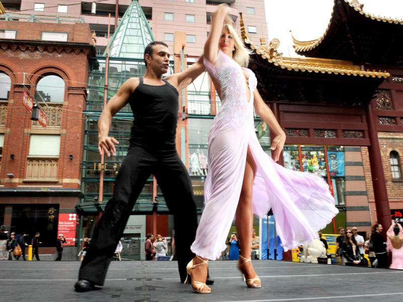 Jessica Raffa (R) and Carmelo Pizzano (L) dance in Melbourne's Chinatown in front of the lunchtime crowds.