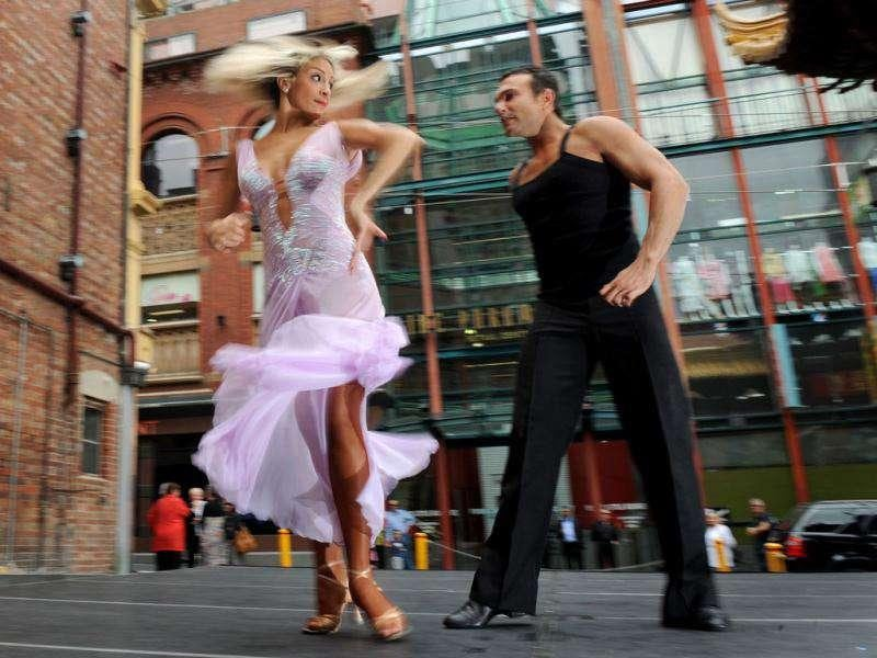 Jessica Raffa (L) and Carmelo Pizzano dance in Melbourne's Chinatown in front of the lunchtime crowd.