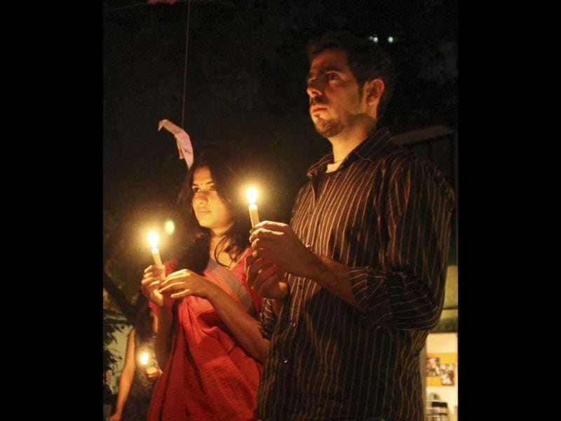 Students hold candles during a prayer ceremony to commemorate victims of 26/11 attacks, in Ahmedabad. Reuters photo