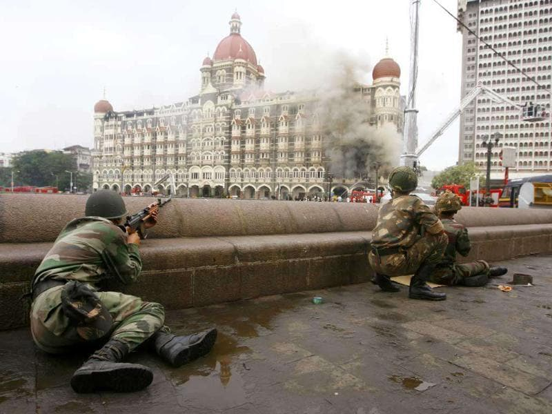 Army men take position during a gun battle at the Taj Mahal hotel (seen in the background) in Mumbai. Operations by commandos were undertaken to dislodge militants at the Taj. Reuters/Desmond Boylan