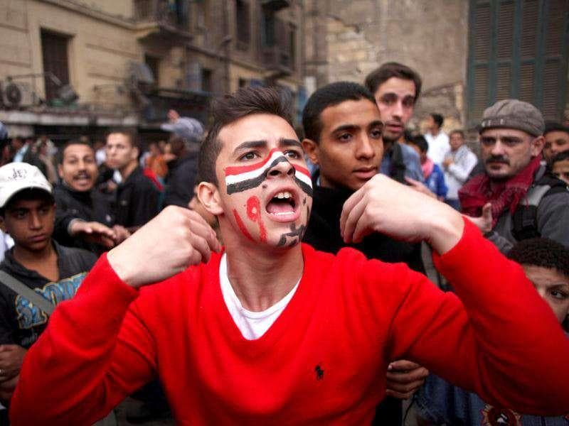 An Egyptian protester with colours of the Egyptian flag and Arabic writing that reads