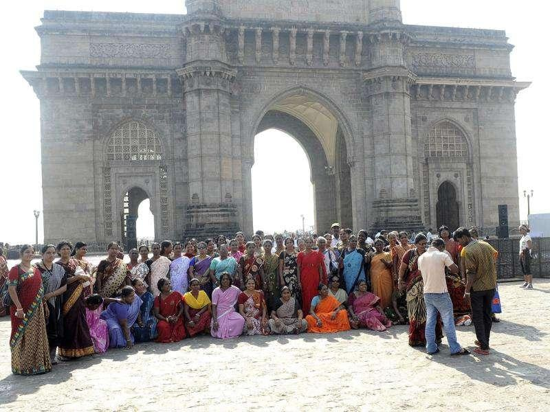 Tourists gather for a group photograph in front of the Gateway of India opposite the landmark Taj Mahal and Palace Hotel on the third anniversary of the 2008 militant attacks in Mumbai.