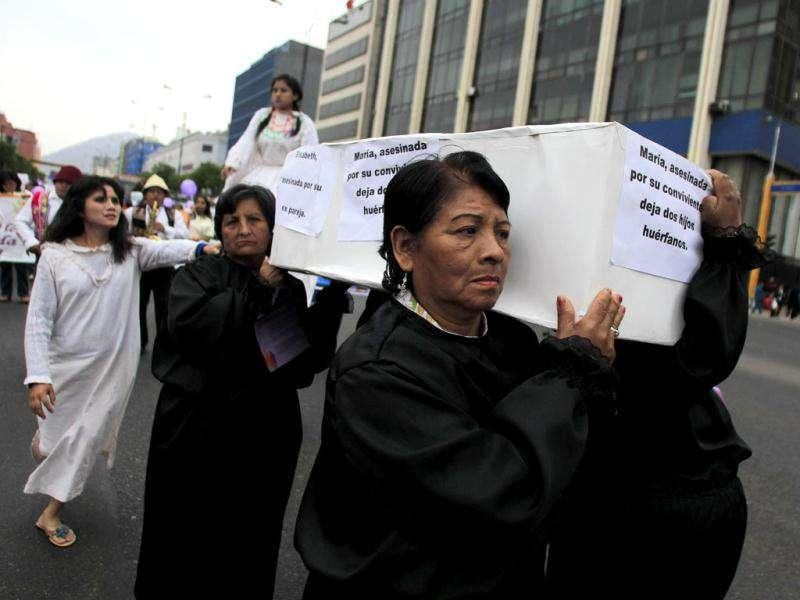 Women in black carry a cardboad coffin in memory of victims of domestic violence during the International Day for the Elimination of Violence against Women march in Lima. The sign reads: