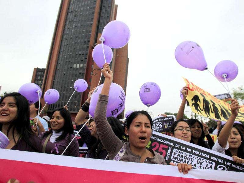 Demonstrators holding balloons participate in a demonstration during the annual International Day for the Elimination of Violence against Women march in Lima. (REUTERS/Pilar Olivares)