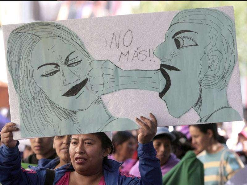 A woman holds a sign that reads,