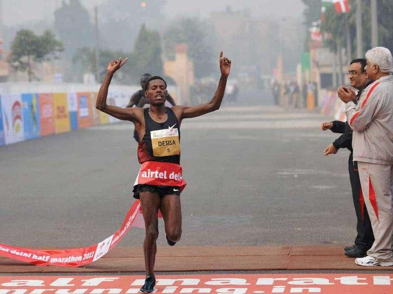 Lelisa Desisa of Ethiopia gestures as he crosses the finishing line for victory in the Airtel Delhi Half Marathon 2011 in New Delhi.