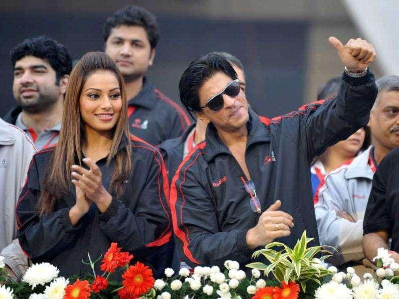 Bipasha Basu (L) and Shah Rukh Khan gesture to fans at the Airtel Delhi Half Marathon 2011 in New Delhi.