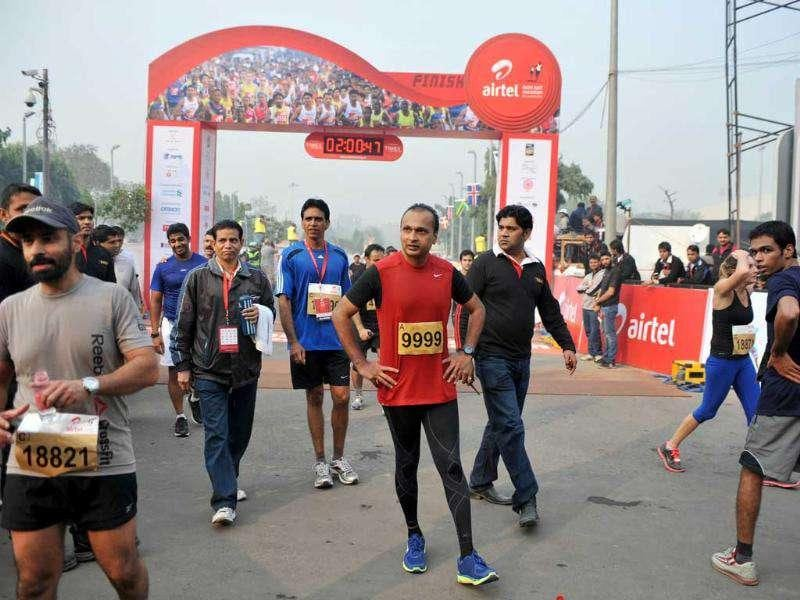 Industrialist Anil Ambani, chairman of Reliance Anil Dhirubhai Ambani Group, pauses after crossing the finishing line of the Airtel Delhi Half Marathon 2011 in New Delhi.