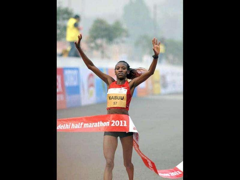 Kenyan athlete Lucy Kabuu celebrates as she crosses the finishing line of the Airtel Delhi Half Marathon 2011 in New Delhi.