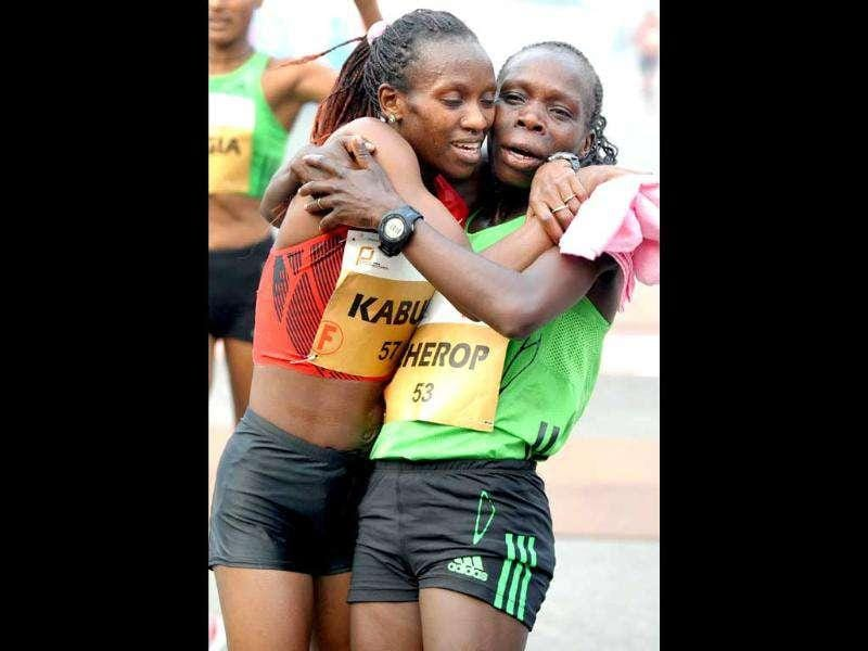 Kenyan athlete Lucy Kabuu (L) celebrates with compatriot Sharon Cherop after crossing the finishing line of the Airtel Delhi Half Marathon 2011 in New Delhi.