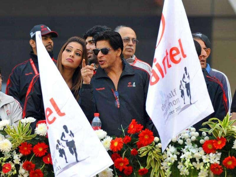 Bollywood actors Bipasha Basu and Shah Rukh Khan gesture as runners pass by during the Airtel Delhi half marathon 2011 in New Delhi.