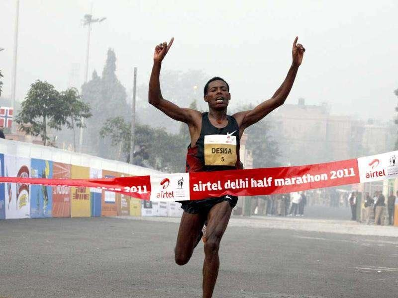 Ethopian Lelisa Desisa crosses the finish line in 59.30 minutes to win the overall men's title at the Airtel Delhi Half Marathon.