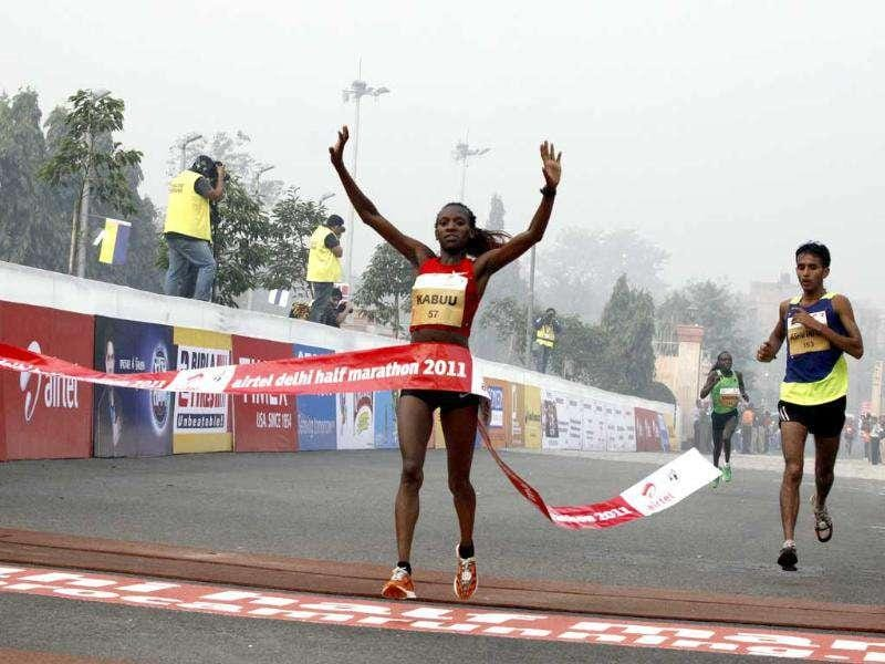 Kenya's Lucy Kabuu crosses the finish line in 67.04 minutes to win the women's overall title at the Airtel Delhi Half Marathon.
