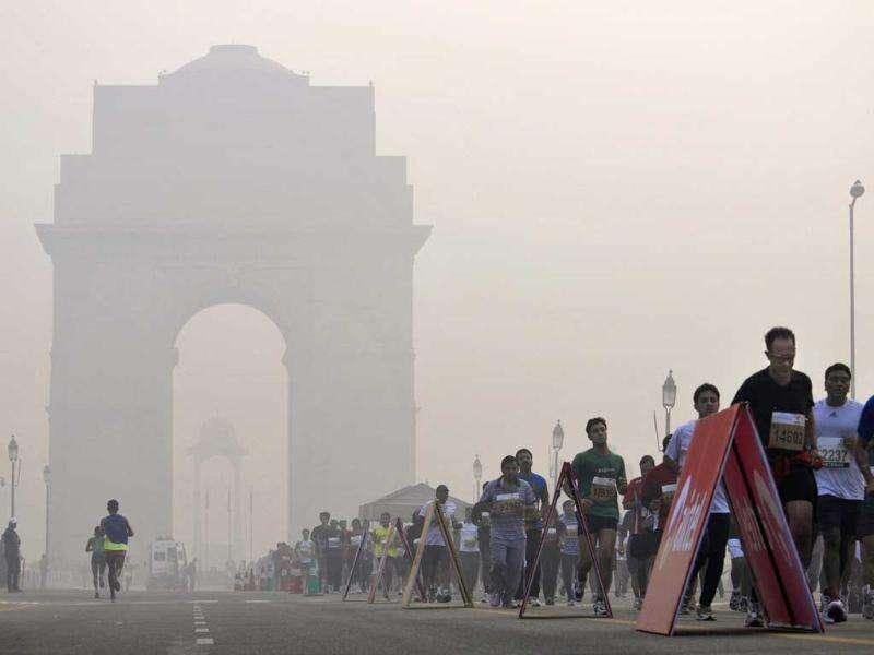 Competitors run as the India Gate monument is seen in the hazy background during the Airtel Delhi Half Marathon in New Delhi.