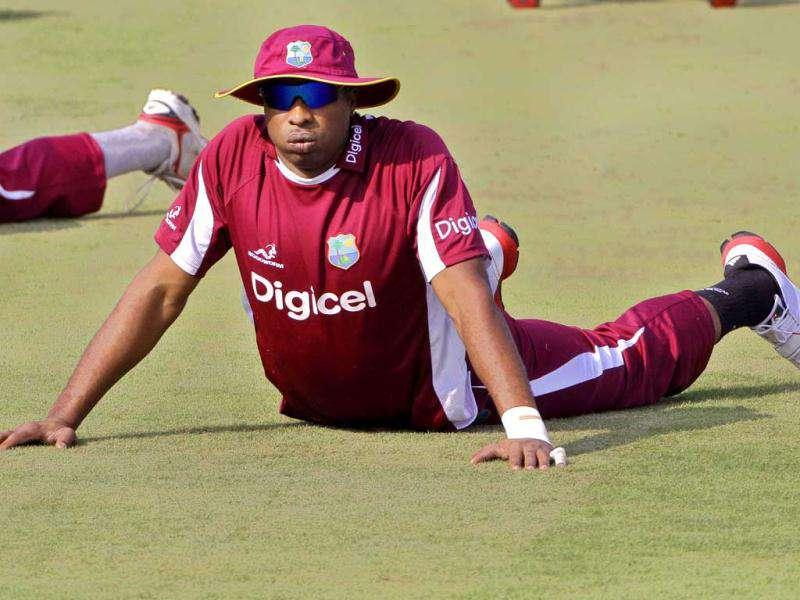 West Indies' Kieron Pollard stretches during a practice session prior to the first one day international cricket match against India in Cuttack.