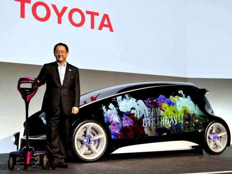 Toyota Motor president Akio Toyoda displays the company's concept model Fun-Vii, which can display various graphics on the interior or exterior of the three-seater vehicle, such as a change of body color and design sent by a smartphone, in Tokyo. AFP Photo/Yoshikazu Tsuno