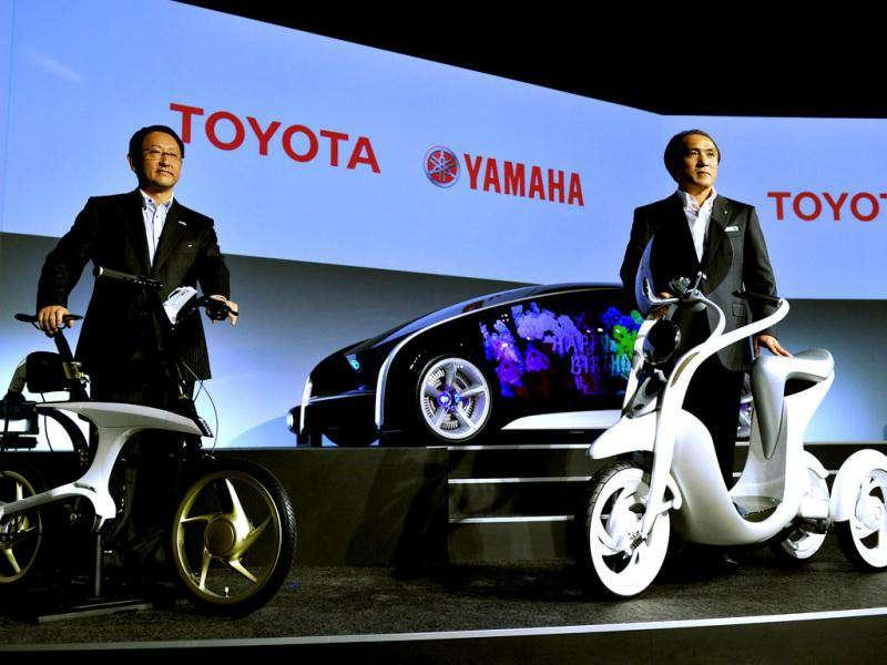 Toyota Motor president Akio Toyoda (L) and Yamaha Motor president Hiroyuki Yanagi display the electric commuter EC-Miu (R) and electric power assisted bicycle Pas With in Tokyo. Toyota and Yamaha have collaborated to design next generation personal vehicles, to be displayed at the upcoming Tokyo Motor Show. AFP Photo/Yoshikazu Tsuno