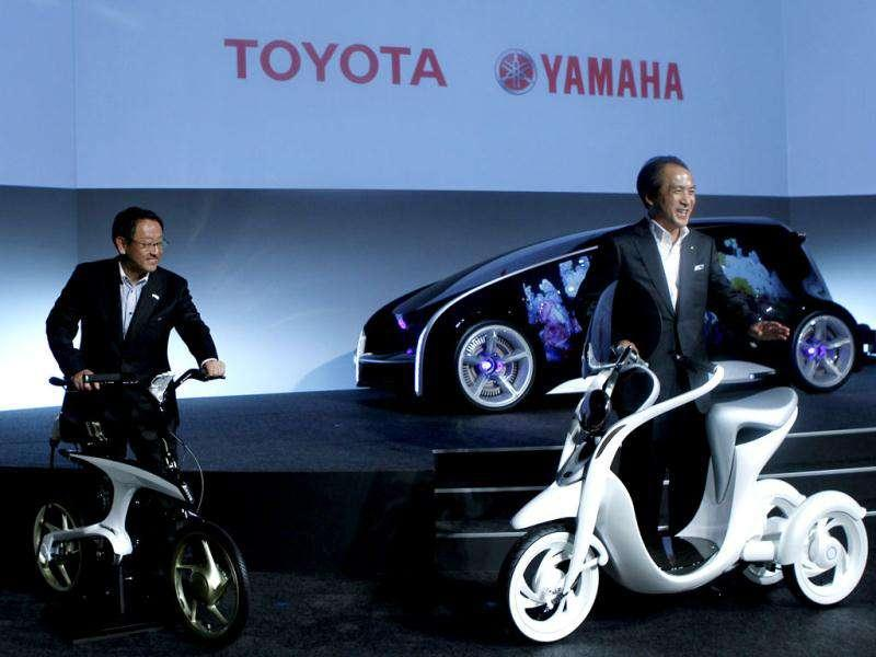 President and CEO of Toyota Motor Corporation Akio Toyoda (L) and Yamaha Motor's President Hiroyuki Yanagi pose as they unveil the electronic commuter EC-Miu (R) and the electronically power assisted bicycle Pas With during a pre-Tokyo Motor show reception at its showroom in Tokyo. Reuters/Kim Kyung-Hoon