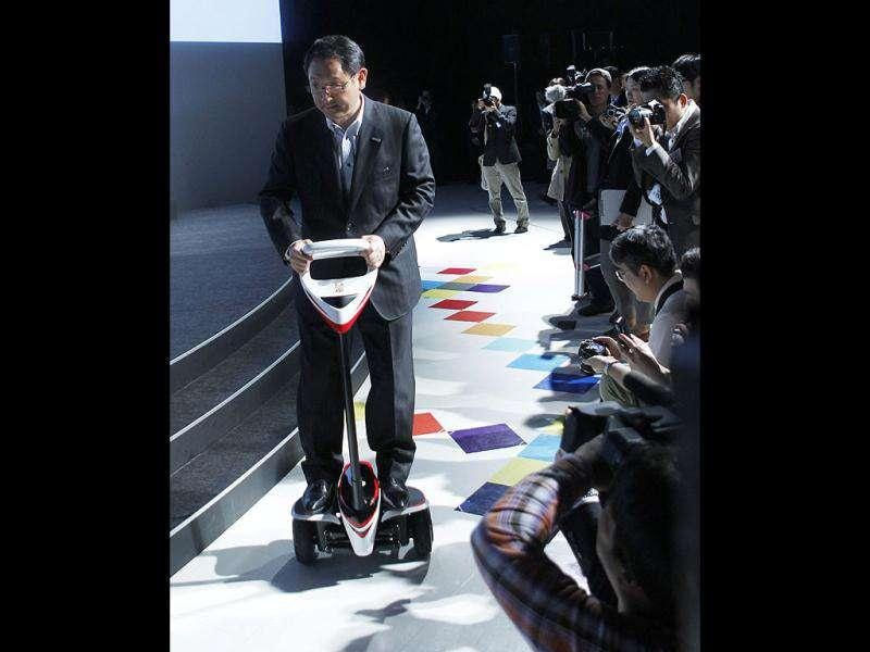 President and CEO of Toyota Motor Corporation Akio Toyoda rides self-balancing two-wheeled scooter Winglet at a pre-Tokyo Motor show reception at its showroom in Tokyo. Reuters/Kim Kyung-Hoon