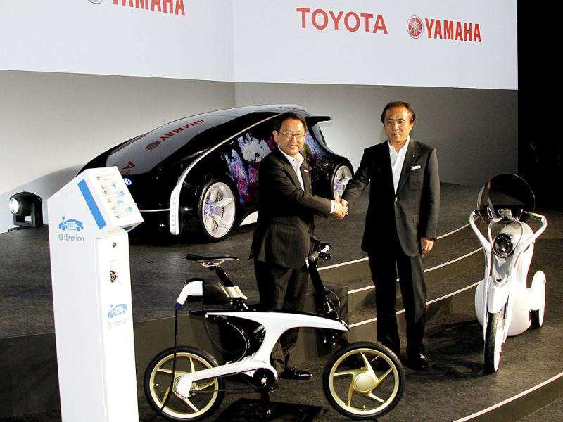 Toyota Motor Corp. president Akio Toyoda (L) shakes hands with Yamaha Motor Corp. president Hiroyuki Yanagi as they unveil next-generation vehicles, the electric commuter bike EC-Miu (R) and the electrically power assisted bicycle Pas With, the two companies are jointly developing during a press event in Tokyo. A vehicle seen in the background is Toyota's futuristic concept vehicle Fun-Vii. AP Photo/Koji Sasahara