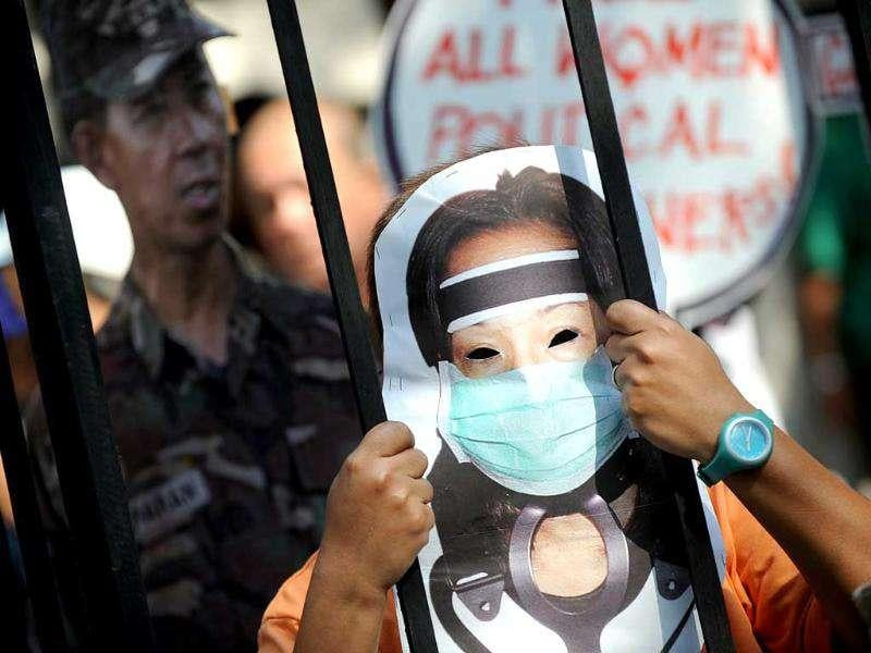 A protester wearing a mask carrying the image of former Philippine president Gloria Arroyo is seen inside a mock prison cell during a demonstration calling for the jaliing of Arroyo in front of the Departrment of Justice building in Manila. AFP Photo/Noel Celis