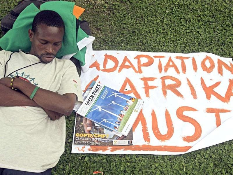 A protestor rests next to his banner during a protest in Durban, South Africa, on the second day of the two-week UN climate conference.