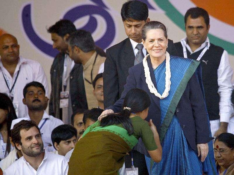 Congress Party President Sonia Gandhi and general secretary Rahul Gandhi look on as a Youth Congress worker seeks blessings at a convention in New Delhi.