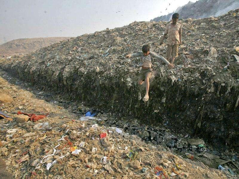 Waste collector Dinesh Mukherjee, 11, watches his friend jump over a puddle of toxic liquid at the Ghazipur landfill in New Delhi. (Reuters)