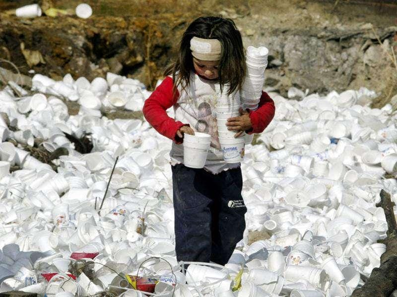 A girl plays with plastic glasses in a garbage dump in a poor slum of Greater Buenos Aires. (Reuters)