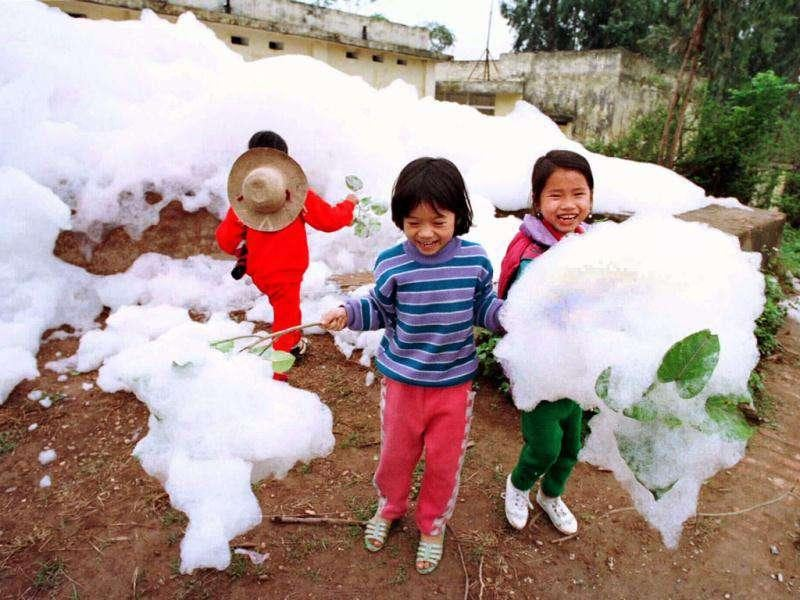 Three smiling Vietnamese girls play by the To Lich River seemingly unaware of the harmfull affects caused by the polluted foam discharged from one of Hanoi's many small rivers. (Reuters)