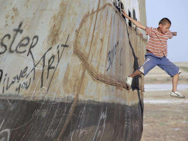 A boy jumps off a derelict boat in the former Aral Sea port of Aralsk.(Reuters)