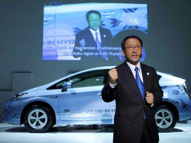 Toyota Motor Corp president Akio Toyoda speaks in front of the company's Prius PHV plug-in hybrid during a news conference at the 42nd Tokyo Motor Show in Tokyo.