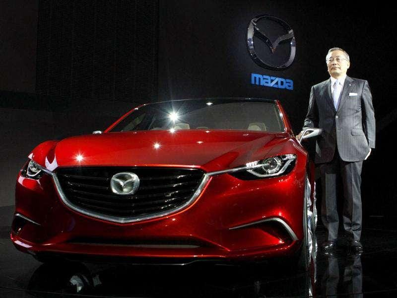 Mazda Motor Corp chief executive Takashi Yamanouchi poses with the company's new concept car Takeri at the 42nd Tokyo Motor Show in Tokyo.