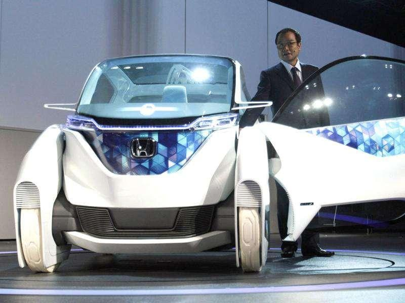 Honda Motor Company president Takanobu Ito speaks next to the company's electric Micro Commuter Concept city vehicle during a news conference at the 42nd Tokyo Motor Show in Tokyo.