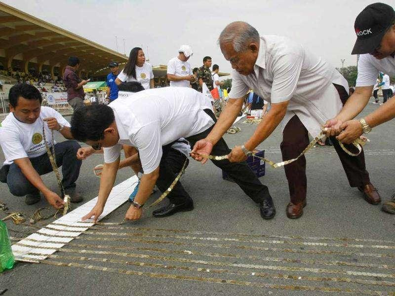 Diwa Guinigundo, second from left, Deputy Governor of the Philippine Central Bank, leads the lining up of 25-Centavo coins in an attempt to break the Guinness World Record. AP