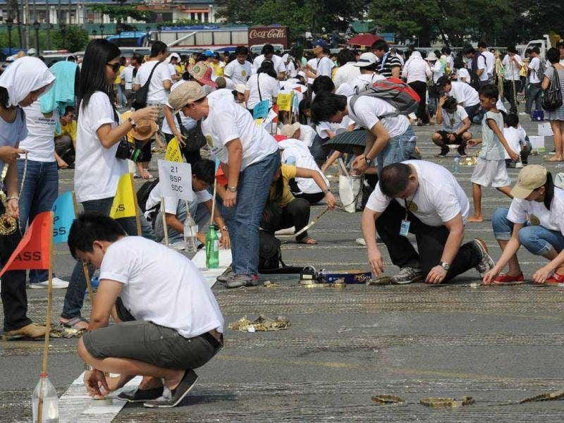 Volunteers arrange Philippine coins on the pavement during an attempt to break the world record of the longest line of coins at Quirino park in Manila. AFP