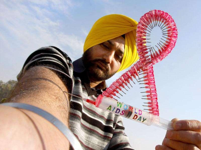 Harwinder Singh Gill a city artist displays his creation as a visual message to spread awareness on the eve of World Aids Day in Amritsar. Munish Byala/HT
