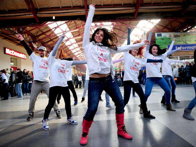 Romanian volunteers dance as they wear t-shirts reading 'I use a condom' at the Gara de Nord railway station during a flash mob, a day before World AIDS Day in downtown Bucharest.