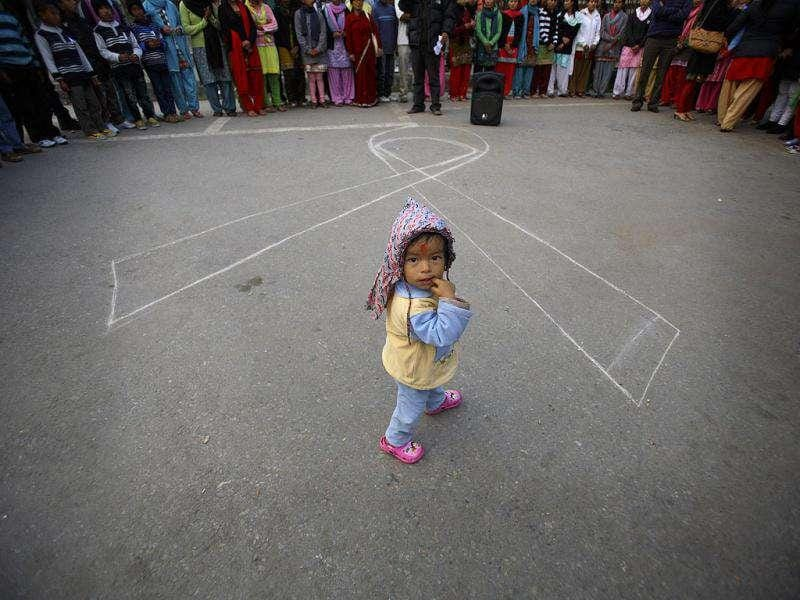 A child looks up while walking past the symbol of a ribbon to mark the upcoming World Aids Day in Kathmandu.