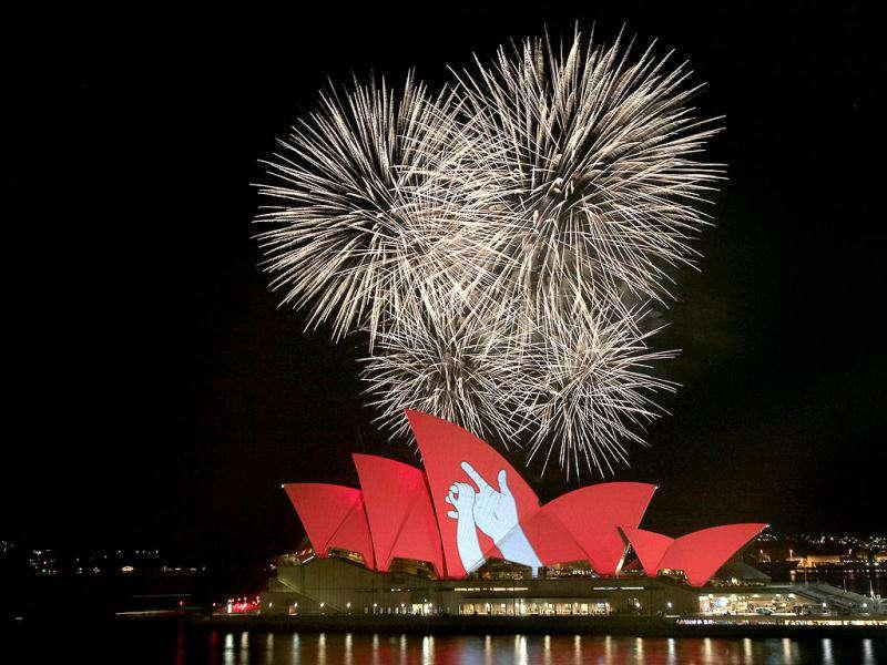 Fireworks burst behind the Sydney Opera House that is bathed in red light with a figure of two hands in Australia as part of a global campaign to create an AIDS-free generation by 2015. Over 50 landmarks and iconic monuments around the world will turn red on Dec 1, in support of the campaign.