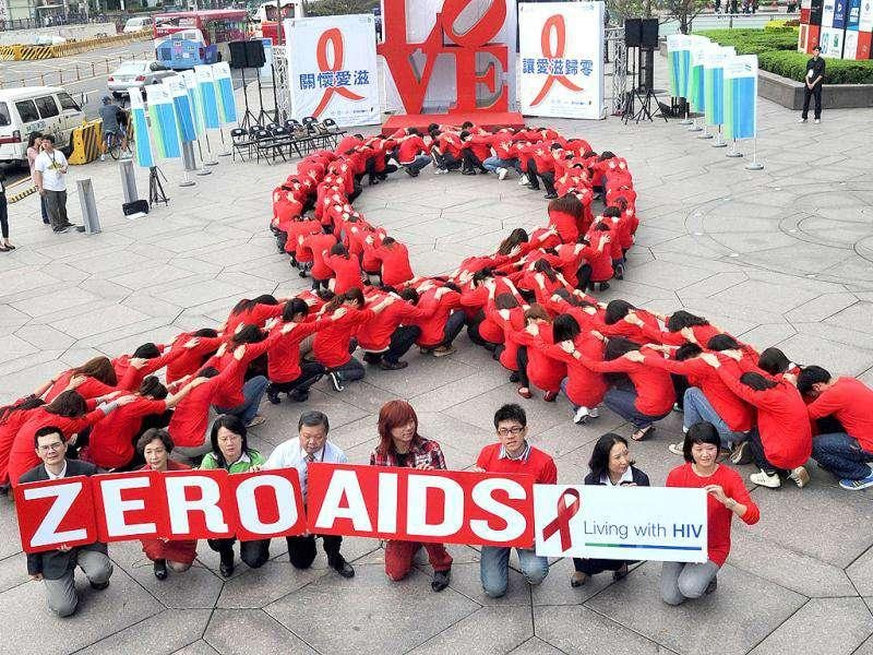 Dozens of volunteers join a human chain in the form of a red ribbon, a symbol of