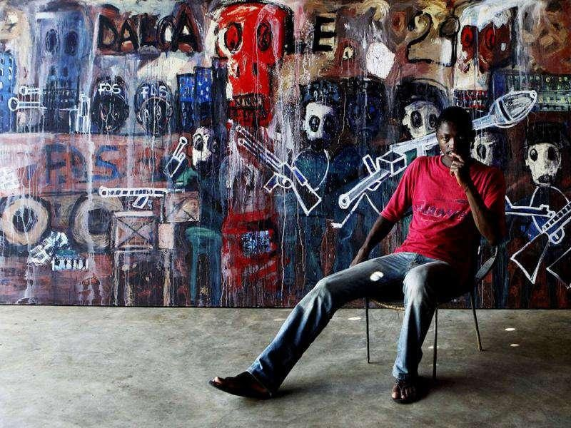 Ivorian painter Abdoulaye Diarrasouba, sits with his work depicting recent upheaval in Ivory Coast's main city Abidjan, in this file photo. The International Criminal Court confirmed former Ivory Coast President Laurent Gbagbo had been detained in The Hague on November 30, 2011, following his arrest on charges of crimes against humanity and transfer from Ivory Coast overnight. (Reuters)