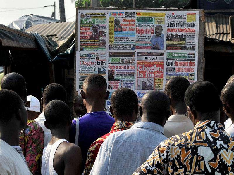People check local newspapers bearing pictures of ex-Ivorian president Laurent Gbagbo in the Abobo neighborhood of Abidjan on November 30, 2011 a day after the transfer of Gbagbo to The Hague. The former Ivorian president was transferred from northern Ivory Coast by charted plane to the Hague-based ICC's detention facility early on November 30, where he is to face four counts of crimes against humanity for his role in the bloody aftermath of disputed presidential polls last year. (AFP Photo)