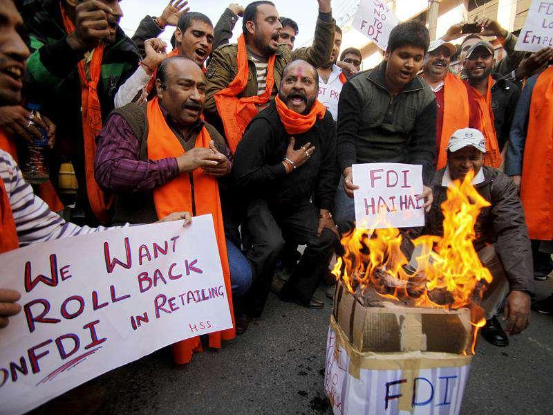 An activist of Shiv Sena, a Hindu hardline group, burns a pamphlet during a protest against Foreign Direct Investment (FDI) in retail sector, in Jammu.