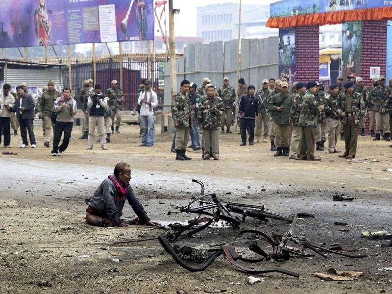 Security force officers stand near a man who was critically injured shortly after an explosion in Imphal, Manipur. The blast occurred near a large fairground close to a convention center that Prime Minister Manmohan Singh is expected to visit later in the week.