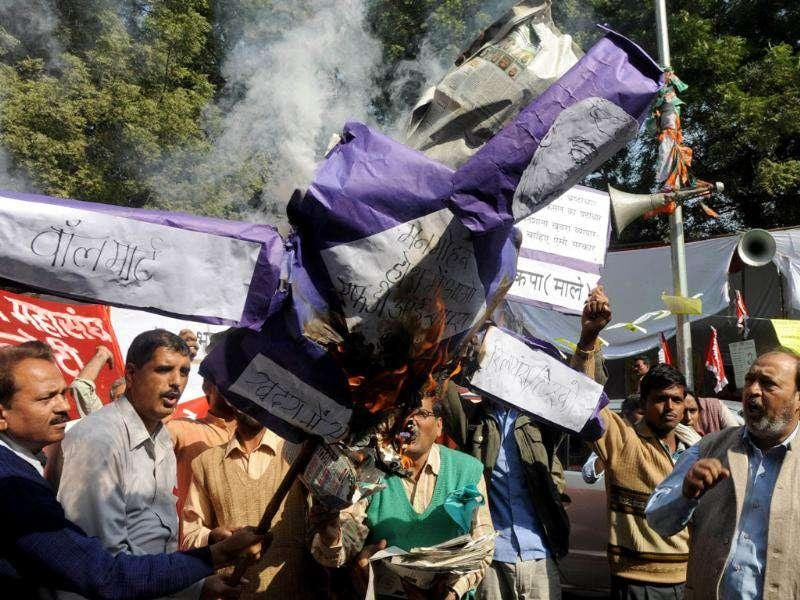 Activists from the CPI-ML shout anti-government slogans as they burn an effigy of Prime Minister Manmohan Singh during a protest against the government's decision to allow 51% Foreign Direct Investment (FDI) in multi-brand retail in New Delhi.