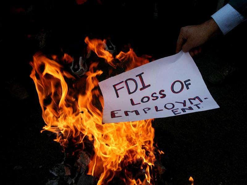 An activist of Shiv Sena, burns a pamphlet during a protest against Foreign Direct Investment (FDI) in retail sector, in Jammu.