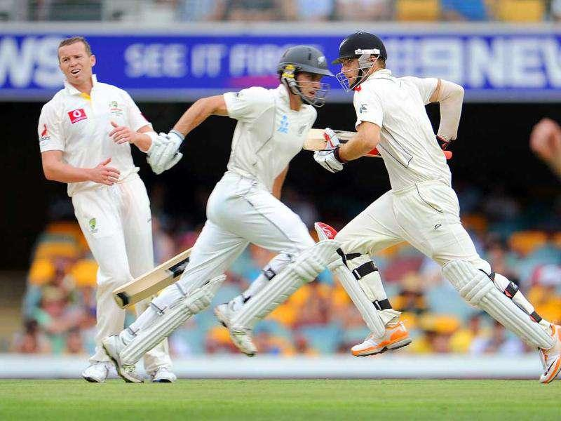 New Zealand batsmen Daniel Vettori (2/R) and Dean Brownlie take runs as Australian paceman Peter Siddle (L) looks on during the first day of their first cricket Test match, at the Gabba in Brisbane.