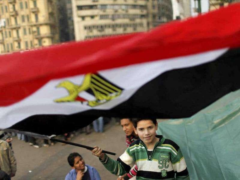 A young protester waves an Egyptian national flag in Tahrir Square in Cairo, Egypt.