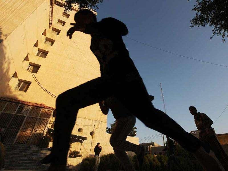 Children play soccer in front of the damaged and shuttered al-Hamra Hotel as the sun sets.